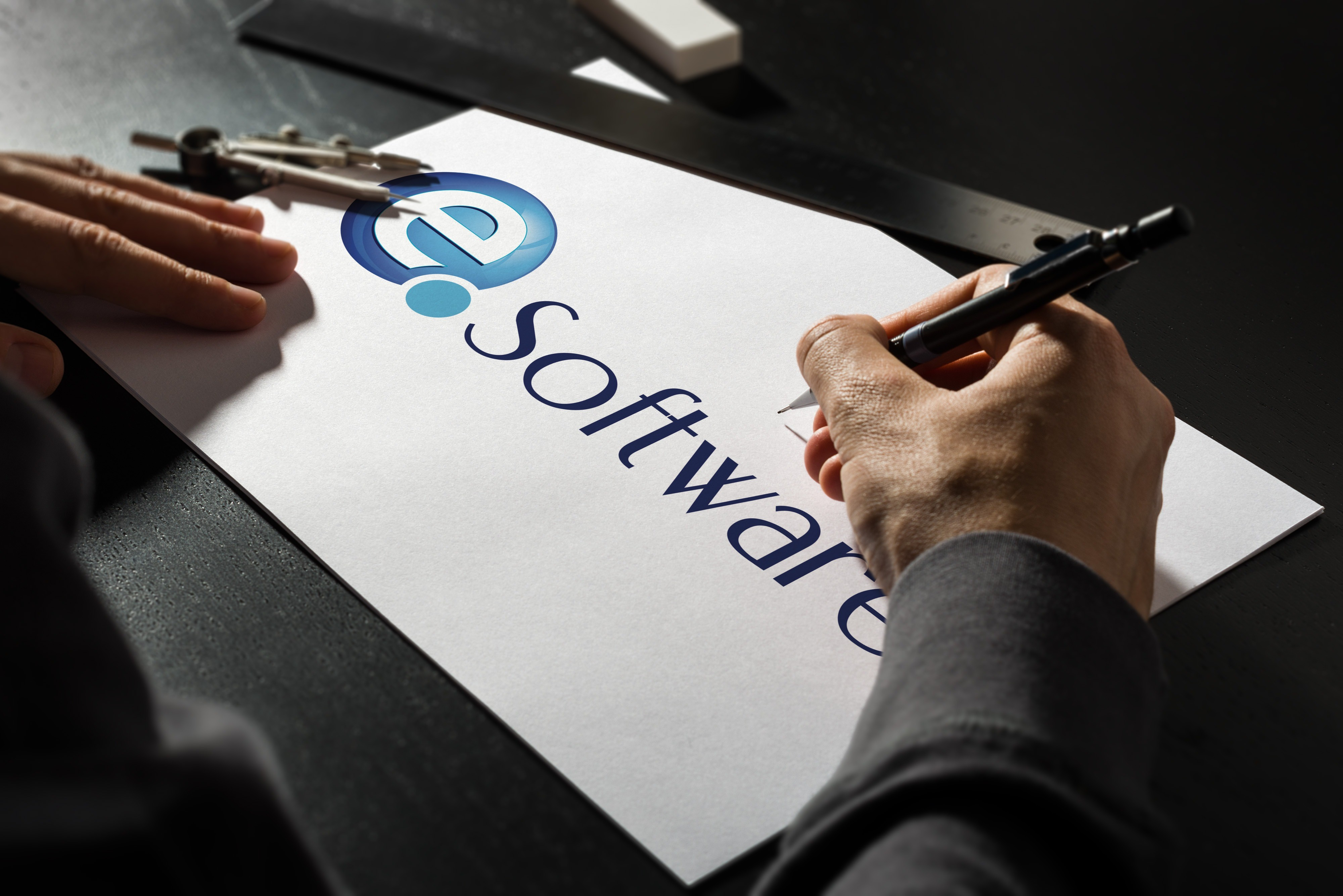 An image showing a person making finishing touches to the EQ Software logo on a sketchpad.