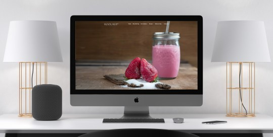 An Apple iMac desktop computer sitting in a contemporary office showing the Kool Kup website on the screen.