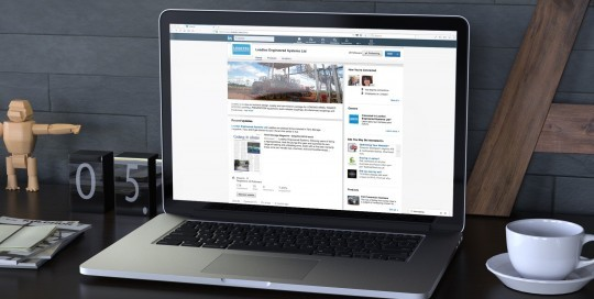 An image of a laptop computer sitting on a work desk showing the LinkedIn company page of Loadtec Engineered Systems on it.