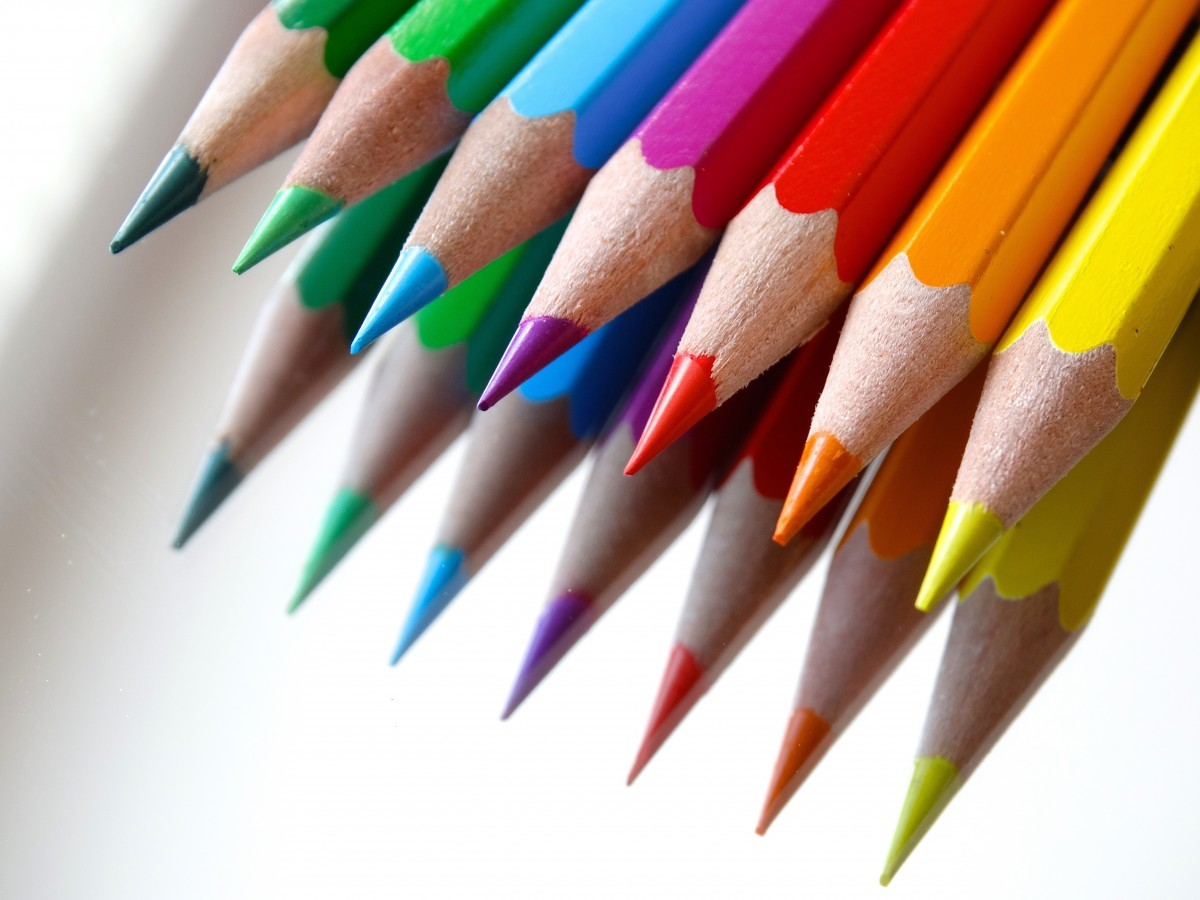 An image of coloured pencils in a row in the top right hand corner, at a 45 degree angle.