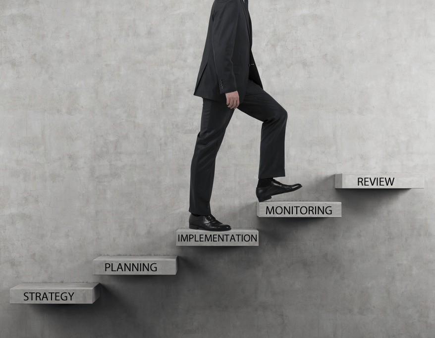An image of a man walking up some open stairs which have words relating to marketing strategy on them.