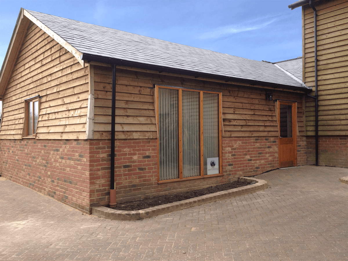 "A photo of the front of the Zein Marketing office from the outside. It is a single storey ""barn"" style building with a half wooden fascia."
