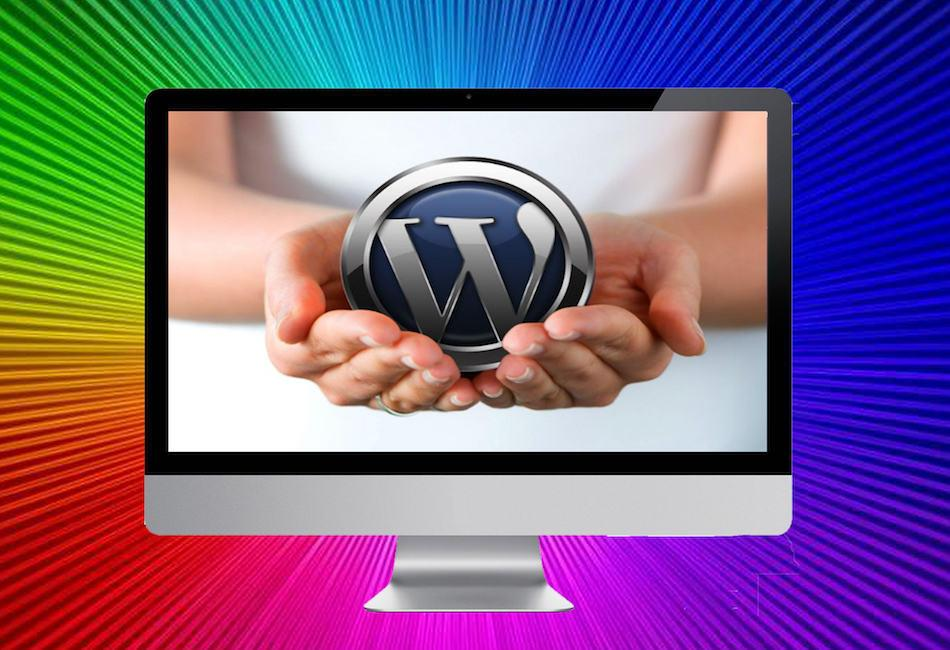 A colour photo of a face on shot of a desktop computer with a multi coloured background. There are two hands cupping the WordPress logo shown on the screen.