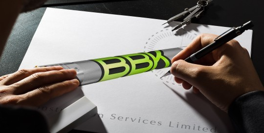 An image showing a person making finishing touches to the BBK Construction Services logo on a sketchpad.