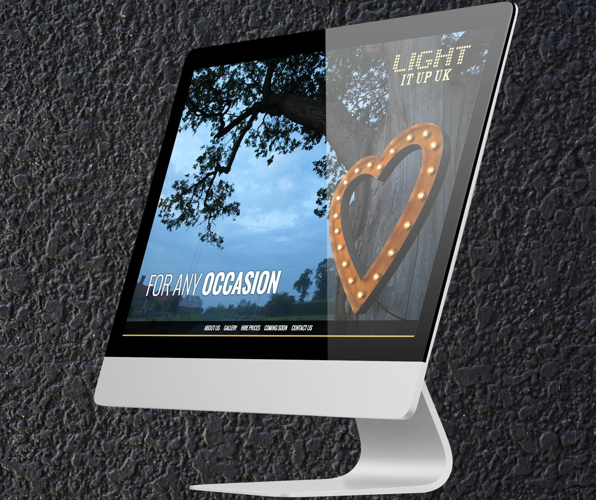 An image showing a desktop computer sitting at an angle and showing the homepage of the Light It Up UK website.