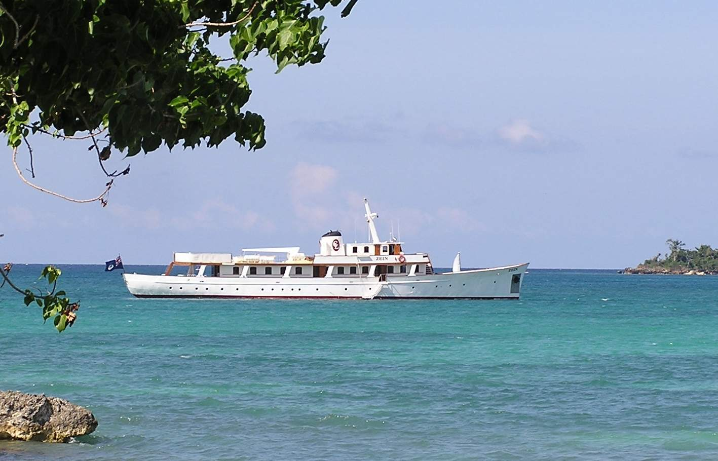 A photo of a white motor yacht sitting in a bay on a sunny day with a tree just showing to the left hand side.