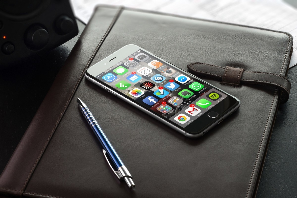 An image of an iPhone laying on a desk showing it's home screen with social media icons on it.