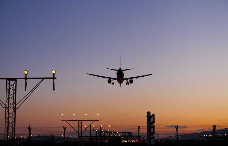 A photo of a plane landing at dusk taken from the ground just behind the runway.