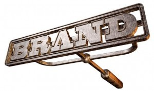 An image of an old fashioned cattle branding iron with the word brand on it.