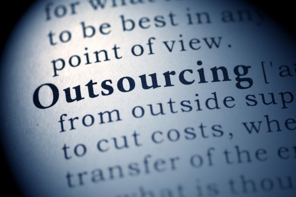 "A close up image of dictionary type book with the word ""Outsourcing"" highlighted."