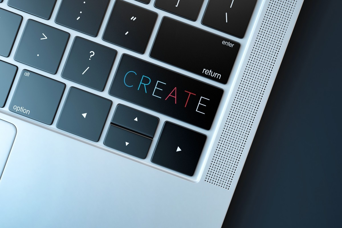 A close up image of the front left hand corner of a laptop keyboard with the word create on the shift key.