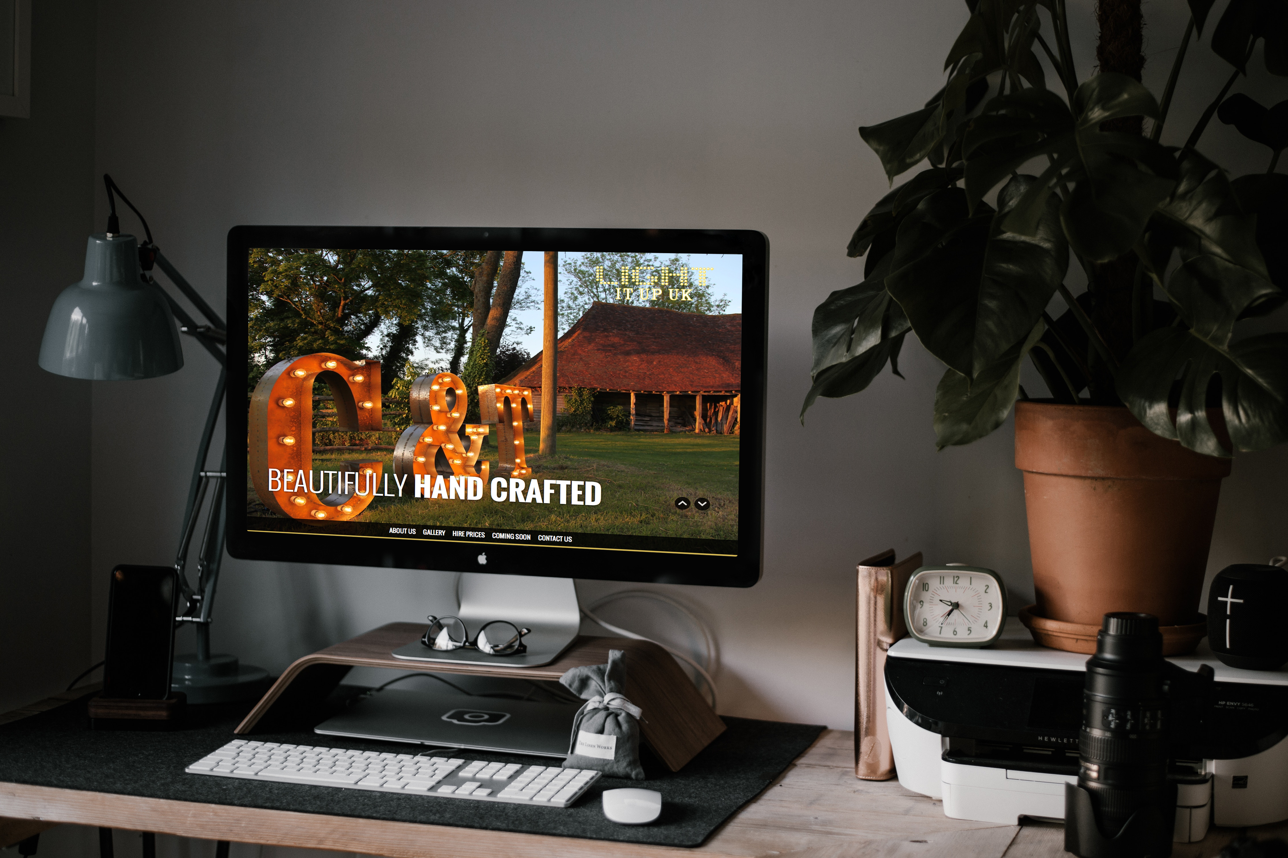 An image showing a desktop computer sitting on a work desk e and showing the homepage of the Light It Up UK website.