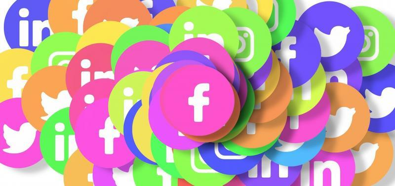 A large pile of fluorescent circular discs with social media icons within them