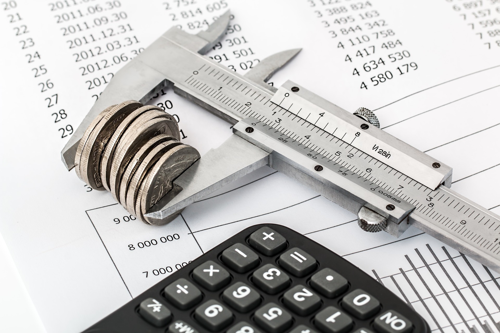 An image depicting a micrometer, some cash, a calculator and a page of figures.