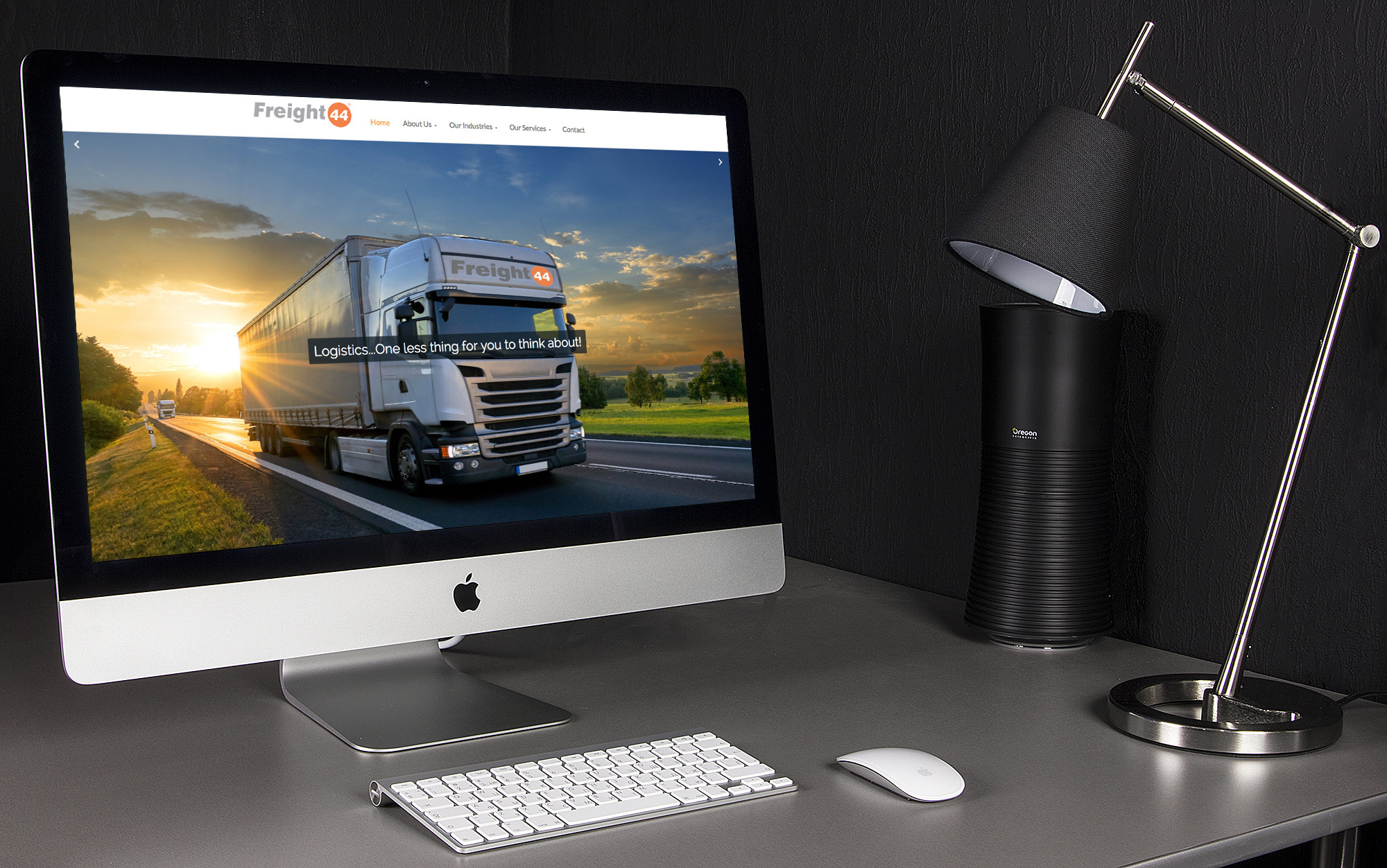 A desk with an iMac on it with the home page of the Freight 44 website open on it.